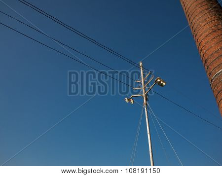 Light pole against blue sky with chimney