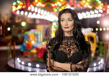 Attractive sexy brunette with black lace blouse posing outdoors with merry-go-round in background