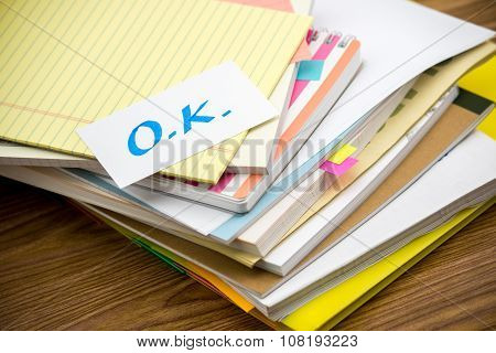 Ok; The Pile Of Business Documents On The Desk
