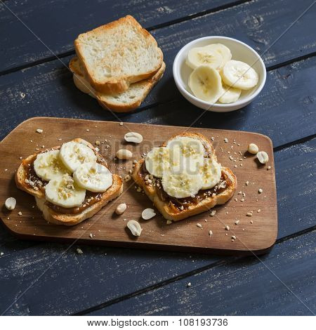 Sandwich With Peanut Butter, Banana And Peanuts, Served On The Board, On A Wooden Surface