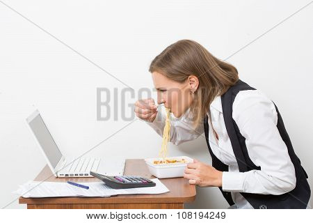 girl eats a pasta, working behind the laptop.