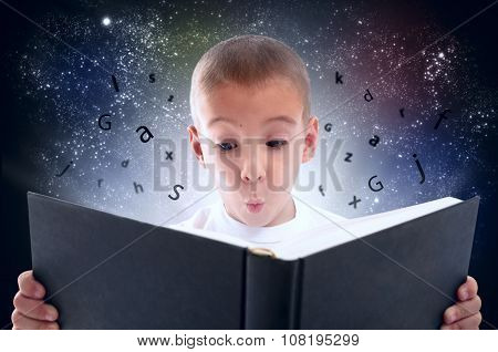 Enthusiastic little boy reading a book on a background the starry sky
