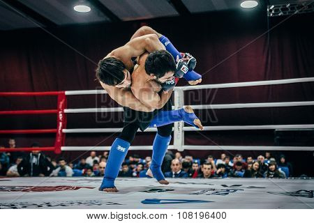 two athletes are fighting MMA in ring