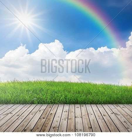 Green grass with wood floor and rainbow in blue sky .