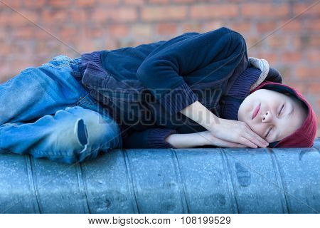 Young Homeless Boy Sleeping On A Heating Pipe