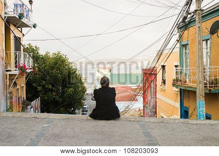 VALPARAISO - NOVEMBER 07: Man at the top of hill street in a district of the protected UNESCO World Heritage Site of Valparaiso on November 7 2015 in Valparaiso Chile