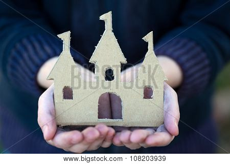 Homeless Boy Holds A Cardboard Castle