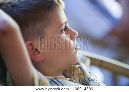 Pensive Child Sitting With Hands Behind Head