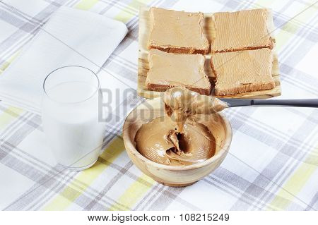 Sandwiches With Peanut Butter On Wooden Plate, Peanut Butter In A Wooden Bowl, Table Knife, A Glass
