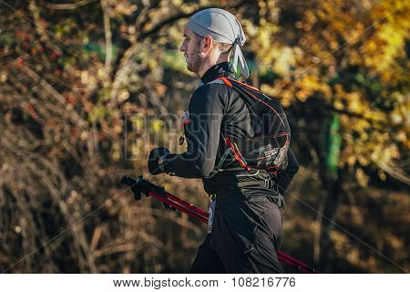 young man athlete running marathon walking sticks