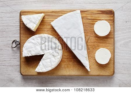Avangard White Soft Cheeses: Goat, Brie, Camembert On Wooden Desk On White Table Top View