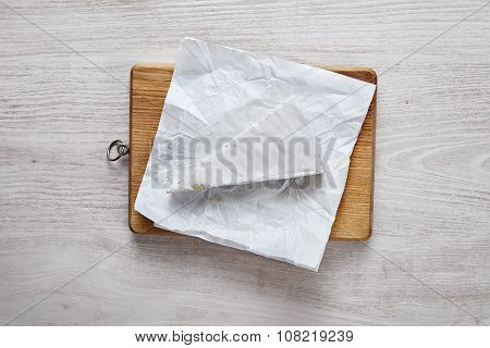 Brie Uncovered On Wooden Brown Plate On White Table Isolated Top View