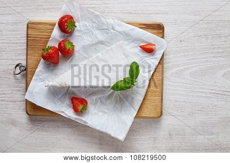 Brie Uncovered On Wooden Plate On White Table With Strawberries