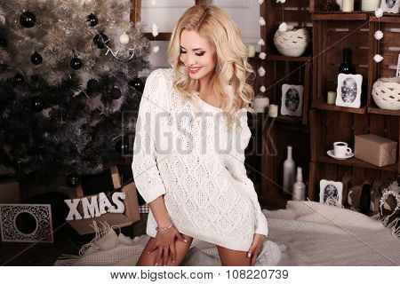 Blond Woman Wears Cozy Knitted Cardigan,posing Beside Christmas Tree