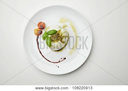 Buffalo Mozarella Topped With Pesto Sause And Served With Cherry Tomatoes On White Plate Isolated To