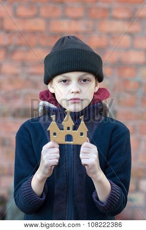 Young Homeless Boy Holds A Cardboard Castle