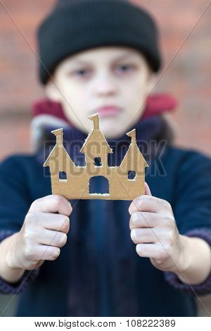 Yong Homeless Boy Holds A Cardboard Castle