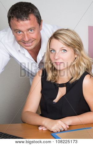 Closeup Of A Smiling Blond Office Worker And Her Boss