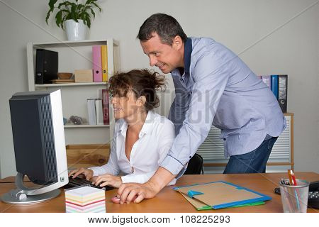 Office Workers In Front Of Computer In A Bright Office
