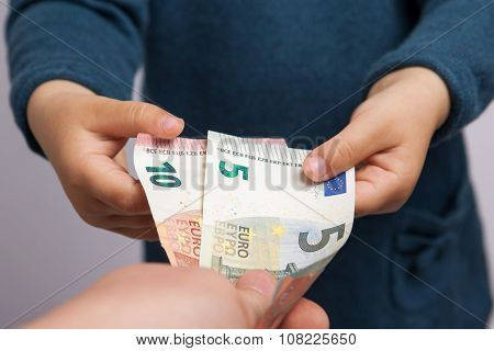 Small Child Hand Takes Five And Ten Euros Banknotes From Adult Hand