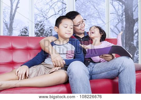 Dad And His Kids Reading Book On Sofa