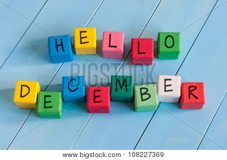 Word Hello December On child's toy cubes on wooden rural  background.