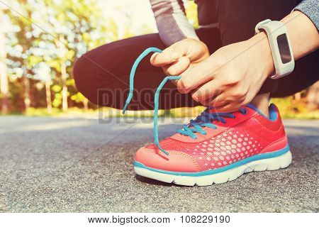 Female Jogger Tying Her Running Shoes For A Jog