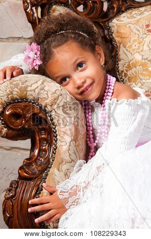 Smiling African  Girl With Curly Hair In A White Lace Dress On Vintage Chair