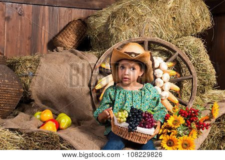 Thoughtful Little African Girl In Cowboy Hat Sitting In The Hay With Fruit