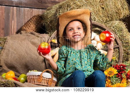 Smiling Little African Girl In Cowboy Hat Sitting In The Hay With Apples