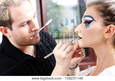 Makeup Artist Applying Lipstick On Model Lips With Brush