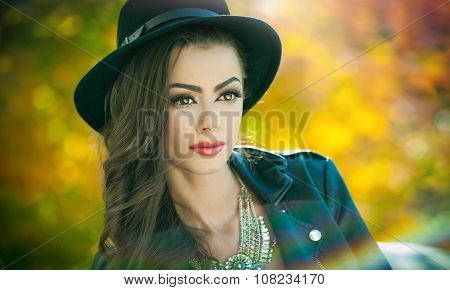 Beautiful woman with black hat posing in autumnal park. Young brunette spending time during autumn