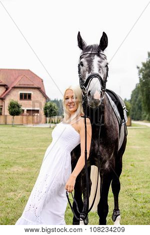 Portrait Of Beautiful Blonde Woman And Gray Horse At The Wedding