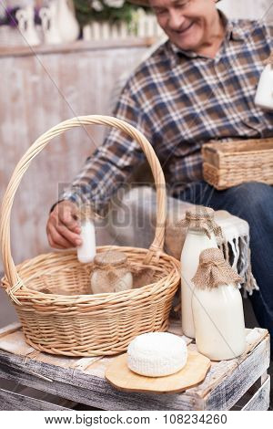 Cheerful old farmer is working with dairy products