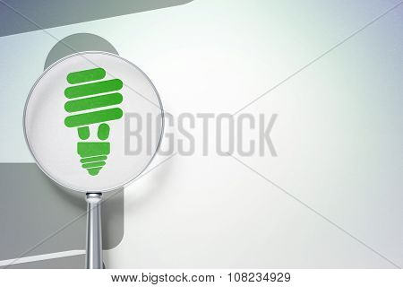 Finance concept:  Energy Saving Lamp with optical glass on digital background