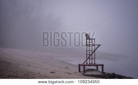 Empty lifeguard chair on a beach on a foggy November morning.