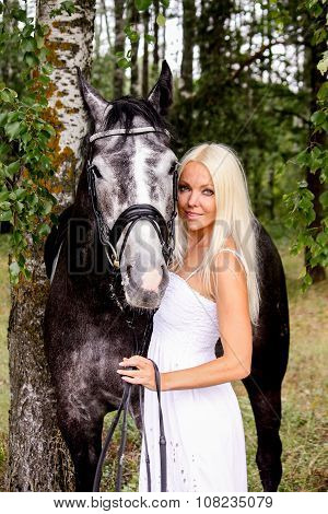 Beautiful Blonde Woman And Gray Horse In Forest