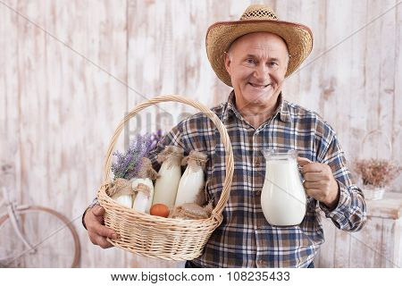 Skilled old farm worker is presenting healthy food