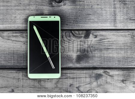 On the wooden table is a smartphone and stylus green