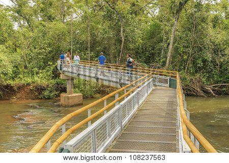Tourists Crossing The Bridge At Parana River In Iguazu Falls