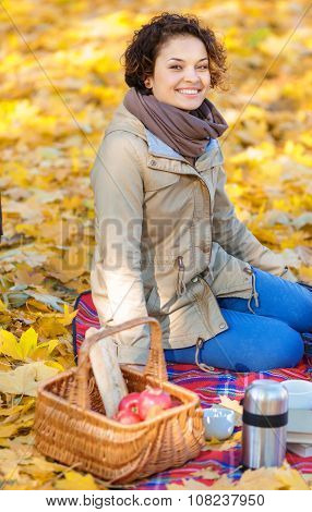Happy woman sitting on the blanket