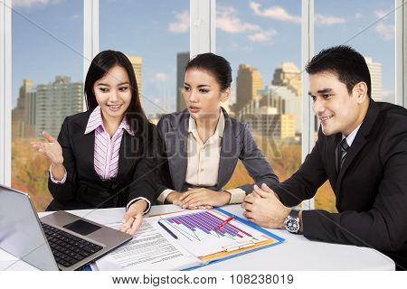 Three Workers Discussing In Office Near The Window