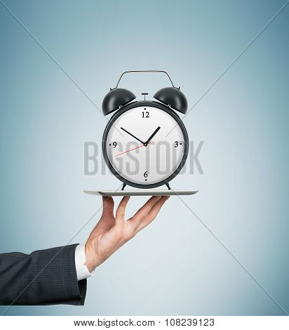 A Hand Holds A Tablet With Alarm Clock. A Concept Of The Time And New Technologies. Light Blue Backg