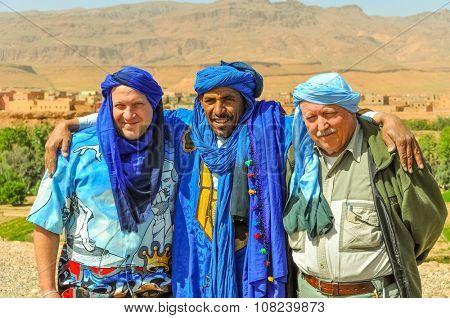 TINERHIR, MOROCCO, APRIL 11, 2015: Local Berber man in traditional attire poses for photos with two tourists in blue turbans near entrance to Todgha Gorge