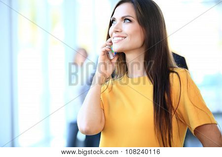 Smiling Confident Business Woman Having A Phone Call With Her Mobile Phone, Office Interior On Backg