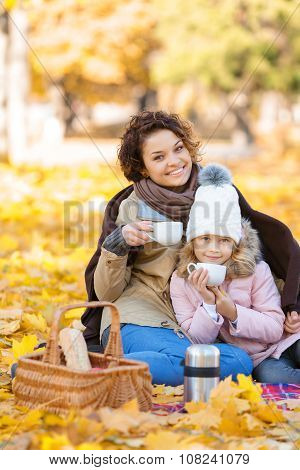 Happy mother and daughter drinking tea