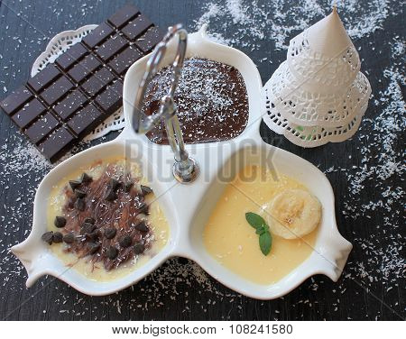 Banana pudding and chocolate pudding in a white vase on a black table in the New Year