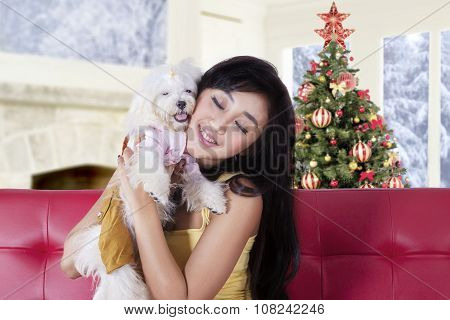 Woman Hugging Her Dog On The Sofa At Home