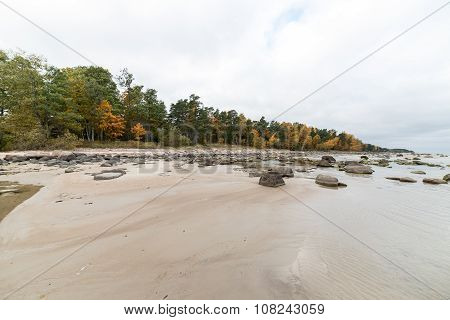 Rocky Autumn Beach With Waves Crashing On The Rocks