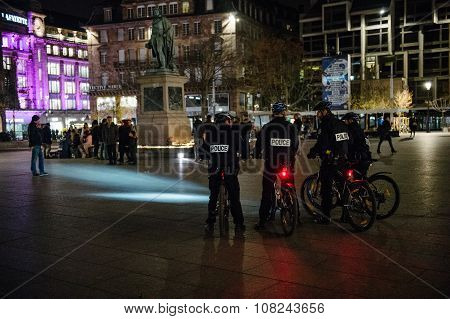 Police Officers On Bike Looking At People And Candles